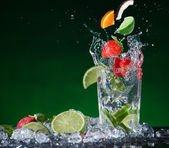 Fresh fruit cocktail in freeze motion splashing — Stock Photo