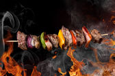 Tasty skewer on black background. — Stock Photo