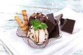 Tasty ice cream scoops on wooden table. — Stock Photo
