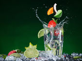 Fresh fruit cocktail in freeze motion splashing. — Stock Photo
