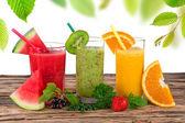 Fresh fruit juices on wooden table — Zdjęcie stockowe