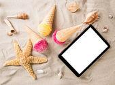 Tasty ice creams with tablet on the beach — Stock Photo