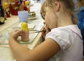 Little girl painting a matrioshka russian doll — Stock Photo