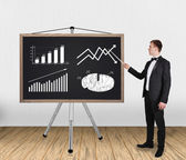 Businessman pointing on chart — Stock Photo