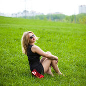 Beautiful young blond woman sitting on the grass. In sunglasses, a black dress, barefoot. — Stock Photo