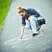 The girl draws a chalk on asphalt — Stock Photo