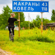 Girl on a bicycle near the road sign — Stock Photo