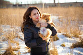 Young girl holding a dog Spitz. Hostess loves his pet. Photographing outdoors — Stock Photo