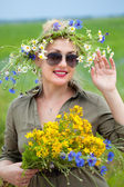 Rustic sweet girl with a wreath of flowers on her head and a bouquet of flowers in her hands waving. — Stock Photo