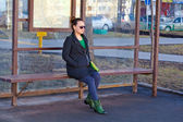 Girl sitting on a bench waiting for transport at the bus stop — Stock fotografie