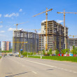 Construction of houses in a new neighborhood, yellow construction cranes. — Stock Photo