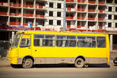 Yellow bus on a background of construction — Stock Photo
