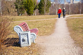 People stroll in the park bench in the foreground. — Stock Photo