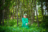Girl in a green dress and hat sitting on his haunches in the forest. fashion Photography — Stock Photo