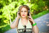 Beautiful young girl in a T-shirt intently listening to music with headphones outdoors — Stock Photo
