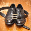 Classic black leather shoes and a leather belt with a buckle on the vintage background — Stock Photo #47032955
