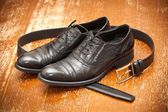 Black leather men's shoes and leather belt — Stock Photo