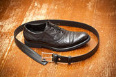 Classic black leather shoes and a leather belt with a buckle on the vintage background — Stockfoto
