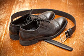 Classic black leather shoes and a leather belt with buckle — Stockfoto