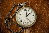 Vintage clock with chain on vintage background — Stock Photo