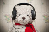 Toy teddy bear with a red scarf listening to music on headphones — Stock Photo