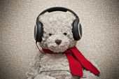 Toy teddy bear with a red scarf listening to music on headphones — Zdjęcie stockowe