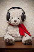 Teddy bear with a red scarf listening to music on headphones — Stock Photo