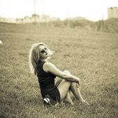 красивая молодая блондинка женщина, сидя на траве. в очки, черное платье, босиком. фото сепия тонированное — Стоковое фото