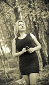 Retrato de una chica hermosa de la naturaleza, en el bosque, en un vestido negro. foto de tono sepia — Foto de Stock