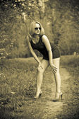 Sexy girl in a dress and shoes in the forest. Sepia toned photo — Stockfoto