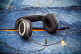 Headphones on a background of blue jeans — Stock Photo