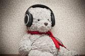ヘッドフォンで音楽を聞いて、赤いスカーフ グッズ テディー ・ ベア — ストック写真