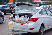 Shopping bags are in the car trunk and grocery cart — Stock Photo