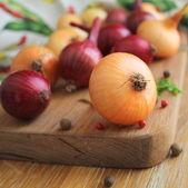 Cebolla roja y amarilla en el tablero de corte — Foto de Stock