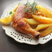Roasted chicken leg with fried potato and lemon — Stock Photo
