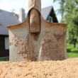 Stock Photo: Shovel sand pile against house