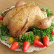 Roasted whole chicken on a plate with vegetables — Stock Photo