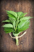 Stinging nettle on a wooden background — Stock Photo