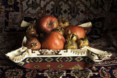 Still life of Armenian pomegranate, apples and carpet — Stock Photo