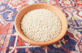 Cereal wheat in the bowl of clay over Armenian carpet — Foto Stock