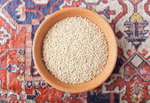 Cereal wheat in the bowl of clay over Armenian carpet — Stock Photo