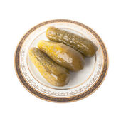 Three marinated cucumbers on the plate isolated over white — 图库照片