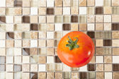 Red sweet tomato over mosaic stone background — Stockfoto