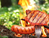 Sausage and steak on a fork. — Stock Photo