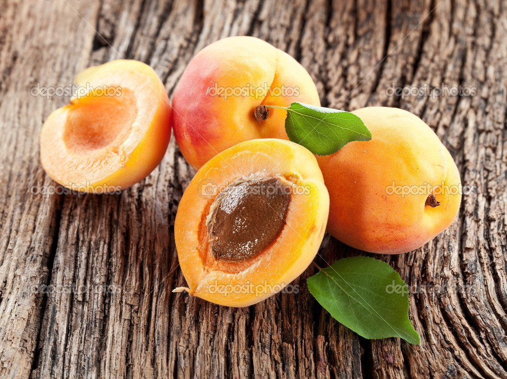 Apricots with leaves on the old wooden table. — Stock Photo #12179057