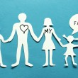 Cardboard figures of the family on a blue background. - Stock Photo