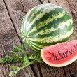 Watermelon with a slice and leaves - Stock Photo