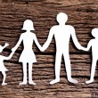 Cardboard figures of the family on a wooden table. - Stock Photo