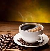 Kaffekopp och fat på ett träbord. — Stockfoto