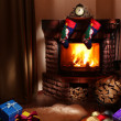Christmas gifts by the fireplace. - 图库照片